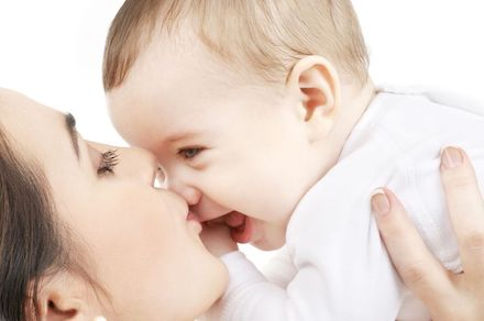 Close up of a mother kissing her smiling baby