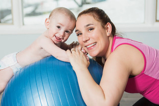 A woman with a baby on an exercise ball