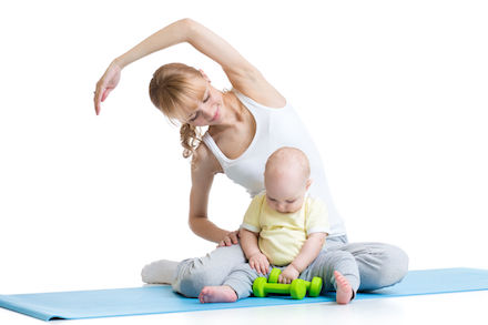 A woman stretches while her baby plays nearby