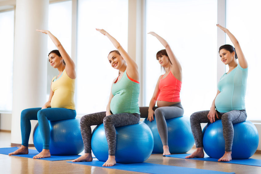 Pregnant women exercising with gym balls.